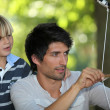 Father teaching his son how to shoot a bow and arrow - Stock Photo