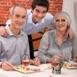 Grandchild with grandparents in restaurant - Stock Photo
