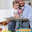 Stock Photo: Father and daughter reading a book