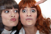 Friends making a silly face against a windowpane — Stock Photo