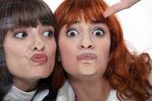 Amici facendo una stupida faccia contro un windowpane — Foto Stock