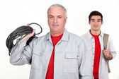 An experienced tradesman posing with his new apprentice — Stockfoto