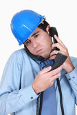 Overwhelmed engineer answering ringing phones — Stock Photo