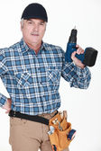 Picture of mature carpenter holding drill — Stock Photo
