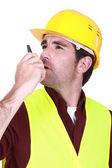 Foreman using radio receiver to delegate work — Stock Photo