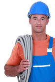 Tradesman carrying corrugated tubing around his shoulder — Stock Photo