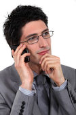 A pensive businessman over the phone. — Stock Photo
