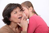 A little girl telling her mother a secret. — Stock Photo