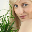 Portrait of blond holding green plant leaf - 