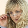 Young woman peering over her glasses at a magazine — Stock Photo #14235887