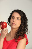 Beautiful young woman holding an apple — Stok fotoğraf