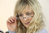 Young woman peering over her glasses at a magazine — Stock Photo