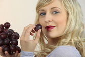 Platinum blonde eating red grapes — Stock Photo