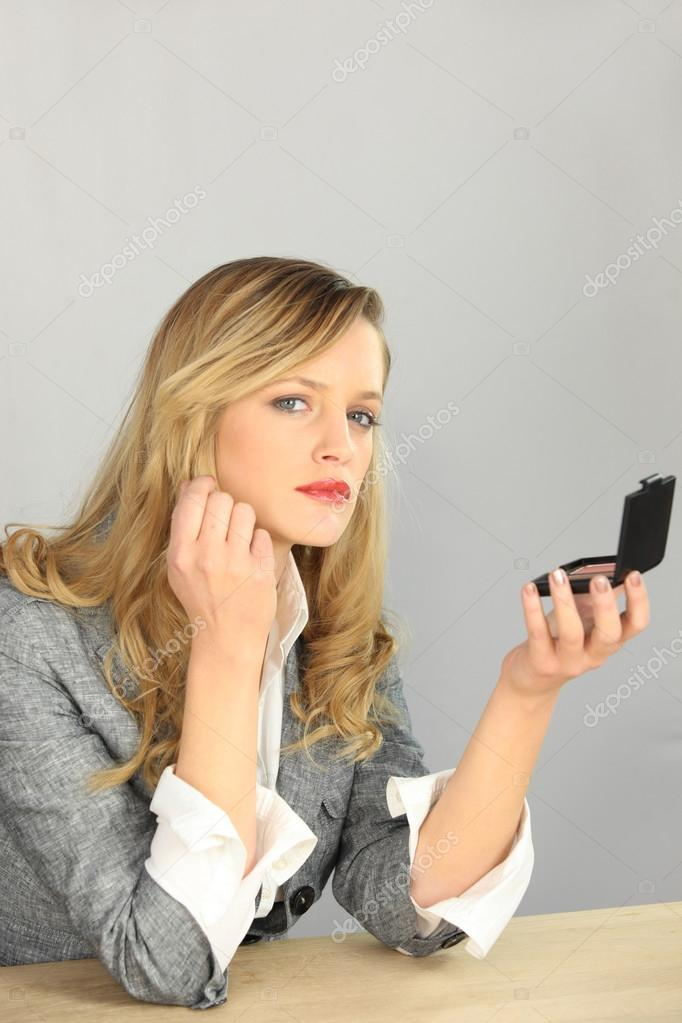 Beautiful woman looking herself in a mirror — Stock Photo #14230413