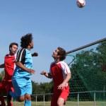 Footballer heading ball towards goal — Stock Photo #14242405
