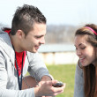 Stock Photo: Couple reading a text message in a field