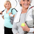 Stock Photo: Two elderly women playing tennis