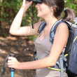 Young woman backpacking and watching landscapes with binoculars - Stock Photo
