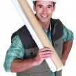 Tradesman holding building drawings — Stock Photo