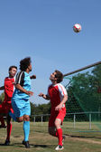 Footballer heading ball towards goal — Stock Photo