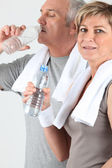 Senior couple drinking water after training — Stock Photo