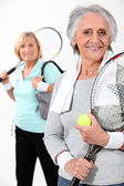 Two elderly women playing tennis — Stock Photo