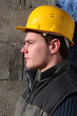 Profile shot of manual worker standing by wall — Stock Photo