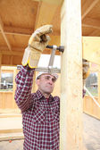 Craftsman making a wooden house — Stock Photo
