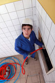 Young man feeding red flexible piping through a large hole in the wall — Stock Photo