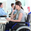 Disabled woman in office - Stock Photo