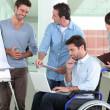Man in wheelchair working with colleagues — Stock Photo #14250569