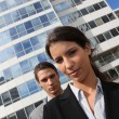 Young couple in suits standing outside an office building — Stock Photo