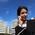 Businesswoman on phone outdoors — Stock Photo
