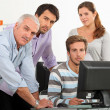 Teacher and students gathered around a computer screen — Stock Photo #14251889