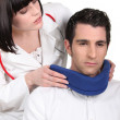 Doctor putting a neck brace on her patient - Stock Photo
