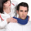 Stock Photo: Doctor putting neck brace on her patient