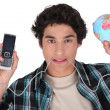 Stock Photo: Young mwith his cellphone plugged into world