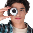 Young man hiding his eye with webcam — Stock Photo
