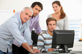 Teacher and students gathered around a computer screen — Stock Photo