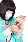 Nurse examining a teddy bear with a stethoscope — Stock Photo
