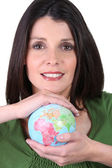 Dark-haired smiling woman holding globe in both hands — Stock Photo