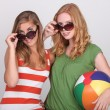 Two young woman with summer shades and a beach ball — Stock Photo #14262147