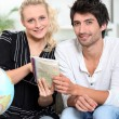 Couple at home looking at maps - Stockfoto