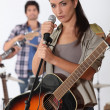 Pretty brunette singing with band — Stock Photo