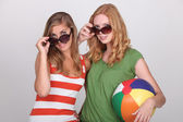 Two young woman with summer shades and a beach ball — Stock Photo