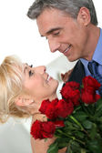 Romantic couple with red roses — Stock Photo