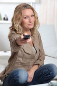 Attractive woman at home using her remote control — Stock Photo