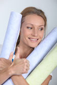 Woman holding rolls of wallpaper — Stock Photo