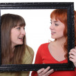 Two women poking heads though empty picture frame — Stock Photo #14272237