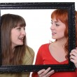 Two women poking heads though empty picture frame — Stock Photo